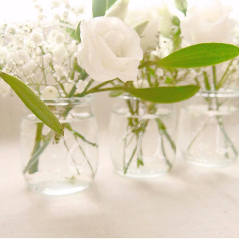 Simple French clear glass yogurt jars repurposed as vases for white blooms - FrenchHue on Etsy. #yogurtjars #vintagestye #vases