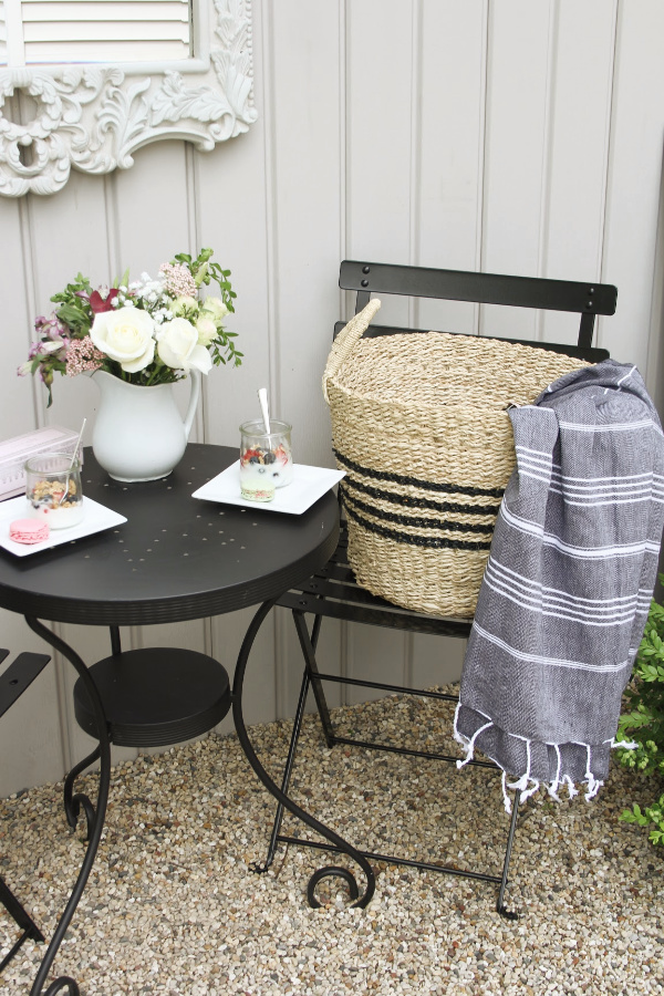 Hello Lovely French country bistro with black dining set, seagrass baskets with stripes, and Turkish stripe throw in a courtyard with gravel. #hellolovelystudio #frenchcountry #outdoordecor #bistroset #outdoordining #outdooroasis #seagrassbaskets #turkishtowel