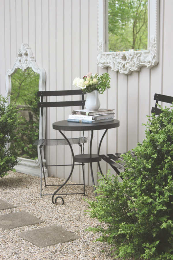 French country style courtyard with pea gravel and black metal modern French bistro dining area and boxwood. #hellolovelystudio #cafechairs #outdoordining #patiofurniture #modernfrench #courtyard #outdoorfurniture
