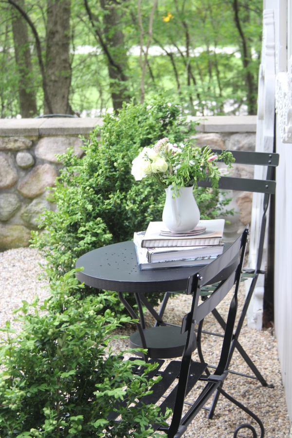 French country style courtyard with pea gravel and stone wall with a black metal modern French bistro dining and boxwood. #hellolovelystudio #frenchcountry #modernfrench #cafechairs #outdoordining #outdoorfurniture #patiofurniture