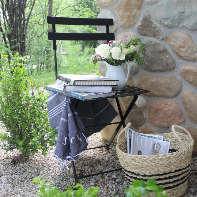Parisian Café Chair stripe Turkish throw tucked in a corner of my garden to invite relaxation and reading (cookbooks are my idea of relaxation!). #hellolovelystudio #frenchcountry #bistrochair #turkishthrow #seagrassbasket #turkishtowel #outdooroasis #romanticgarden #outdoordecor #bistrochairs