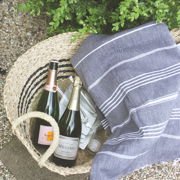 Fancy Parisian style picnic essentials in a black stripe French seagrass basket with Turkish throw. #hellolovelystudio #parisianstyle #frenchcountry #champagne #turkishthrow #frenchpicnic #milieumoment