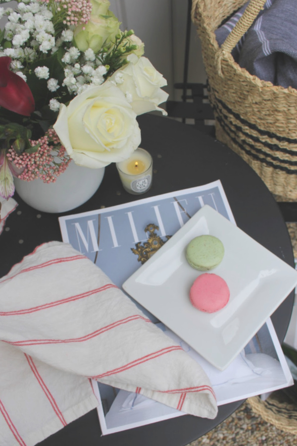 French country blissful vignette with macarons, spring flowers, Milieu magazine, and linen on a tabletop. #hellolovelystudio #frenchcountry #milieumoment #vignette #macarons