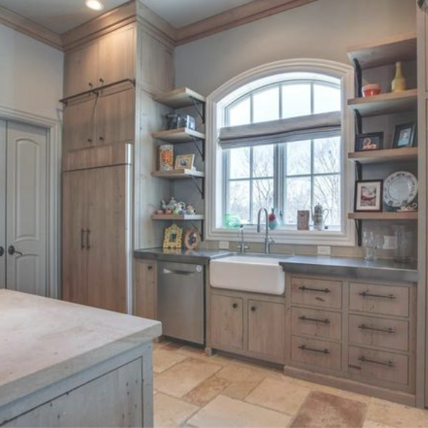 Kelly Clarkson's beautiful farmhouse kitchen in her Tennessee mansion has a farm sink wall with arched window and open shelving. #farmhousekitchen #farmsink #kitchendesign #kellyclarkson #frenchfarmhouse