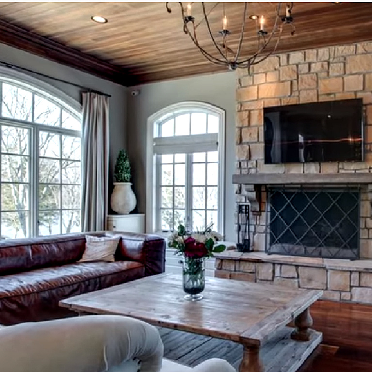 Kelly Clarkson home in Tennessee - a French country inspired den with stone and rustic wood ceiling.