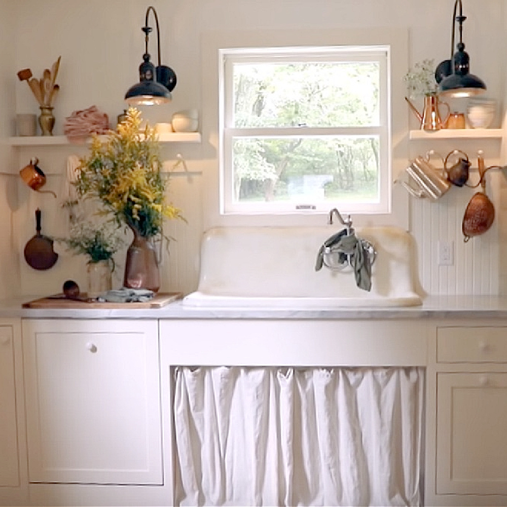 Rustic white cottage kitchen with vintage charm by Leanne Ford in a renovation on Restored by the Fords. #leanneford #rusticdecor #kitchendesign #vintagestyle #farmsink