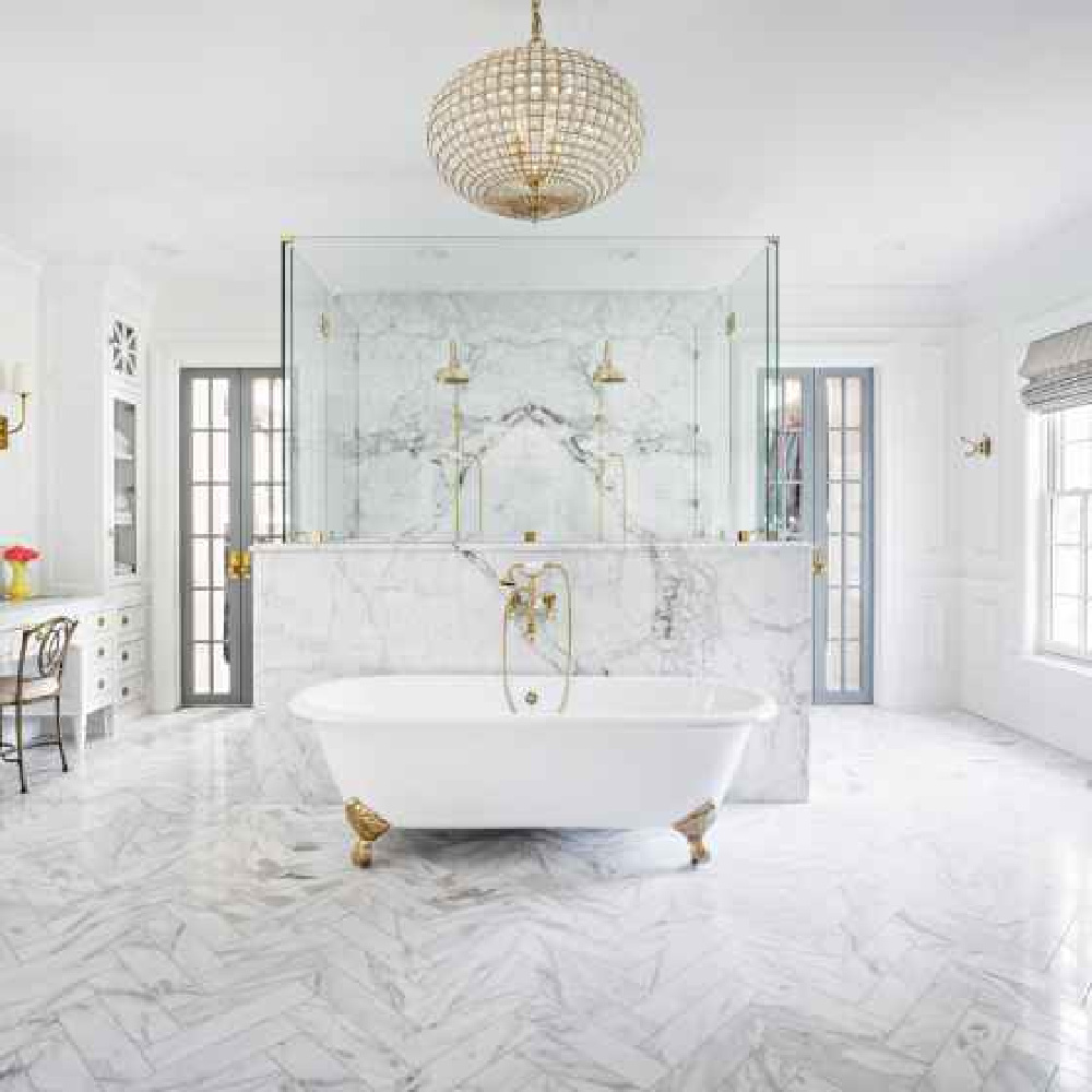Luxurious marble bathroom with clawfoot tub, herringbone marble floor, and symmetrical French doors. Design by The Fox Group. #luxuriousbathroom #bathroomdesign #frenchdoors #thefoxgroup #clawfoottub