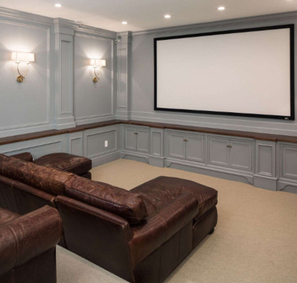 Grey painted paneling in an elegant media room with brown leather sofas by The Fox Group. #mediaroom #thefoxgroup #paneling #greypaneling #brownleather