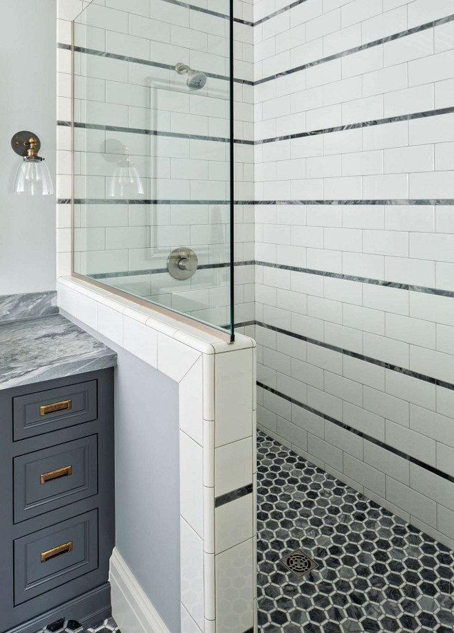 Stripe pattern on tiled showers walls in beautiful classic bathroom by The Fox Group. Hex tiles on shower floor. Come be inspired by more timeless interior design and paint color ideas! #bathroomdesign #thefoxgroup #stripes #timeless