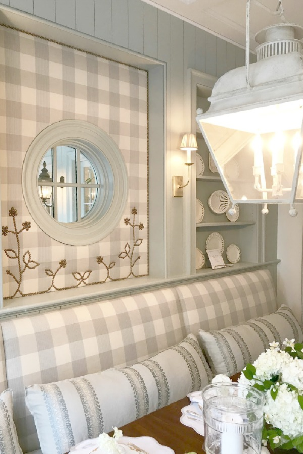 Light blue grey and cream check fabric upholstered walls and banquette in an elegant showhouse breakfast room with vintage lantern pendant. #diningroom #traditionalstyle #gingham #buffalocheck #built-ins #creamware #roundwindow #nailheadtrim #lantern #interiordesign