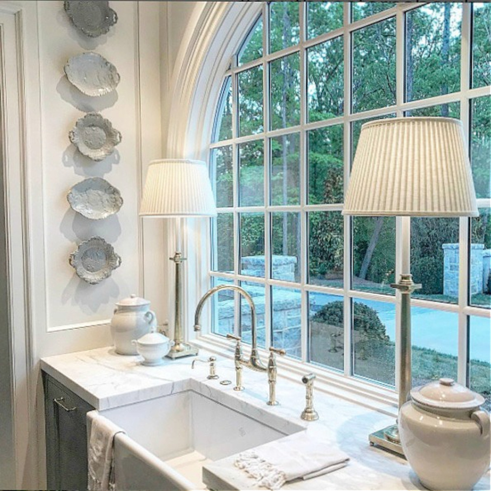 Elegant and traditional style kitchen in Atlanta with arched window at sink and light blue cabinets. #bluekitchen #farrowandballlightblue #timelesskitchen #kitchendesign #traditionalkitchen
