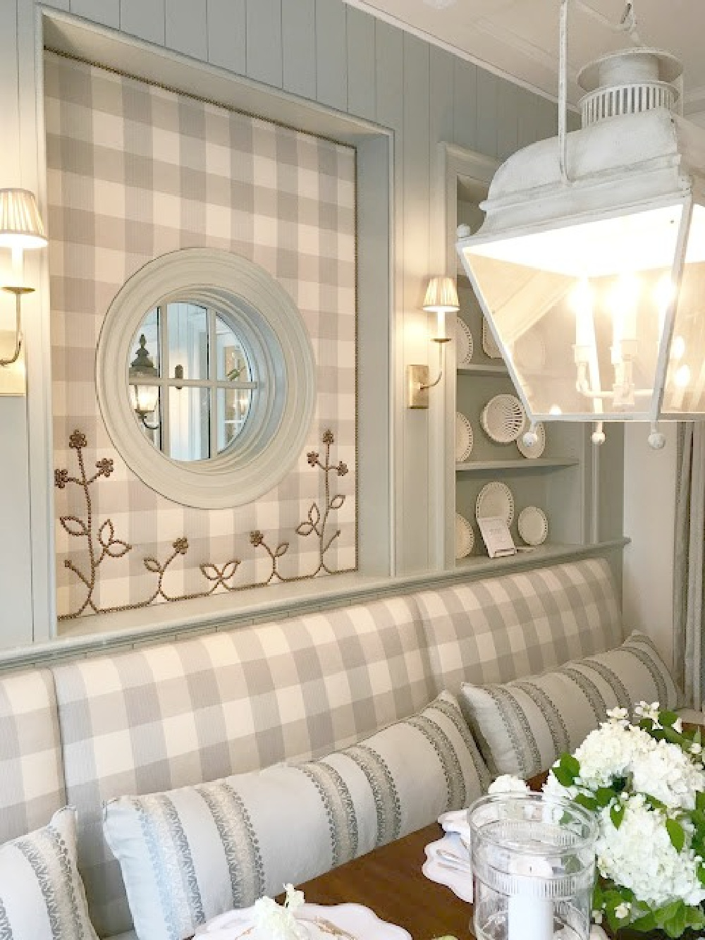 Blue and white Buffalo check upolstered wall and banquette in traditional kitchen breakfast room by Lauren DeLoach.  #buffalocheck #diningroom #interiordesign #lightblue #nailheadtrim #banquette #timelessdesign #traditionalstyle