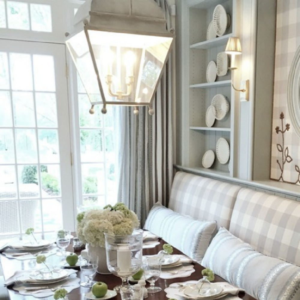 Breakfast dining area in an Atlanta showhouse kitchen has traditional antiques, built-in banquette upholstered in light blue Buffalo check, and bespoke upholstery and drapes. Lauren DeLoach. #diningroom #traditionalstyle #interiordesign #lightblue