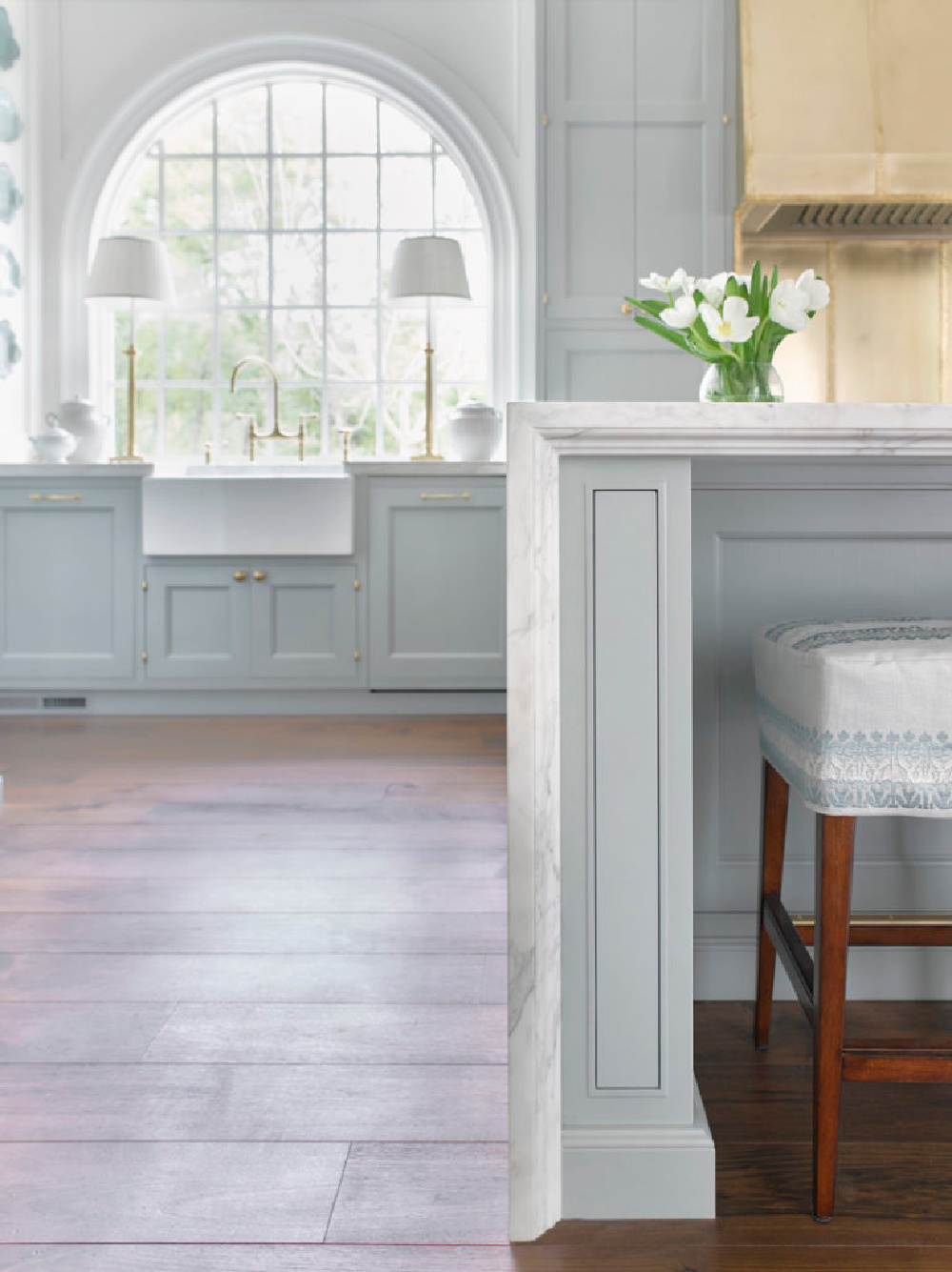 Breathtaking kitchen with light blue by Matthew Quinn. The sink wall with arched window is a shining moment amidst countless others! #bluekitchen #farrowandballlightblue #timelesskitchen #kitchendesign #traditionalkitchen