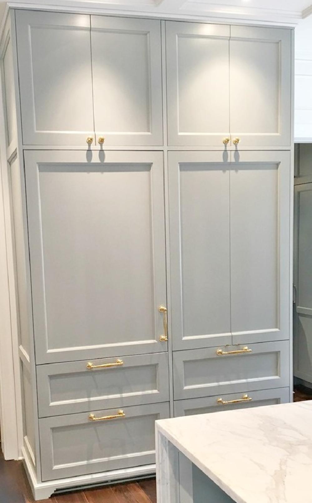 Custom cabinetry in a designer showhouse kitchen is painted Farrow & Ball Light Blue and is enhanced by brass hardware. #bluekitchen #farrowandballlightblue #timelesskitchen #kitchendesign #traditionalkitchen