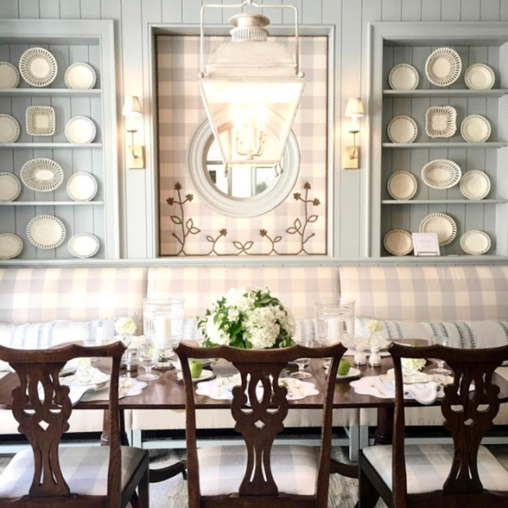Stunning built-in blue painted shelves with lace creamware plates and banquette. #diningroom #traditionalstyle #buffalocheck #lightblue #interiordesign #banquette