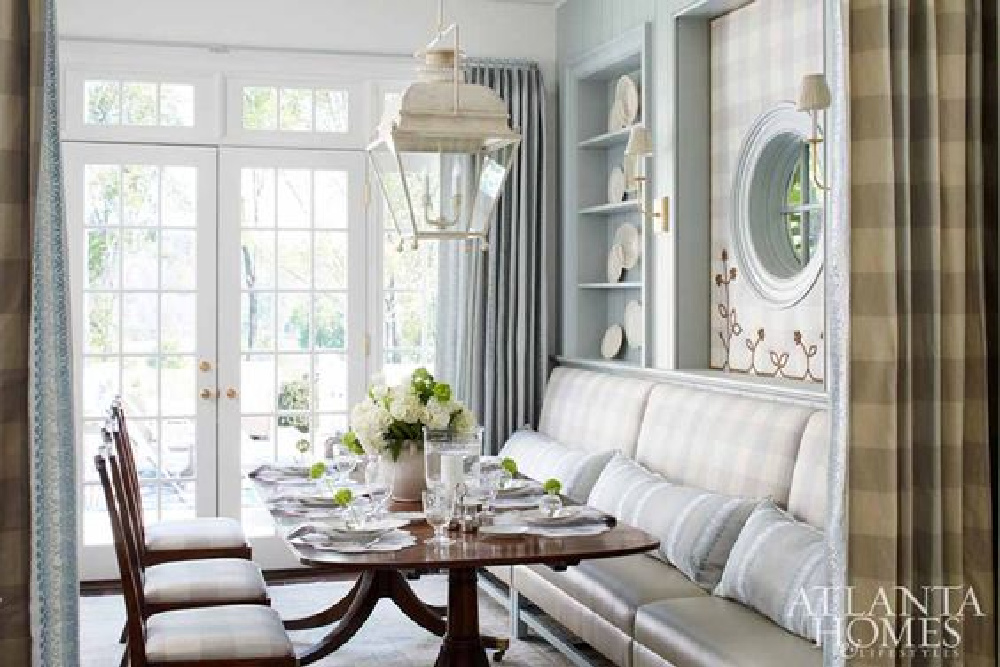 Light blue Buffalo check upholstery, built-in shelves with antique creamware, and custom banquette with round window in a magnificent traditional dining room - Lauren DeLoach is designer.