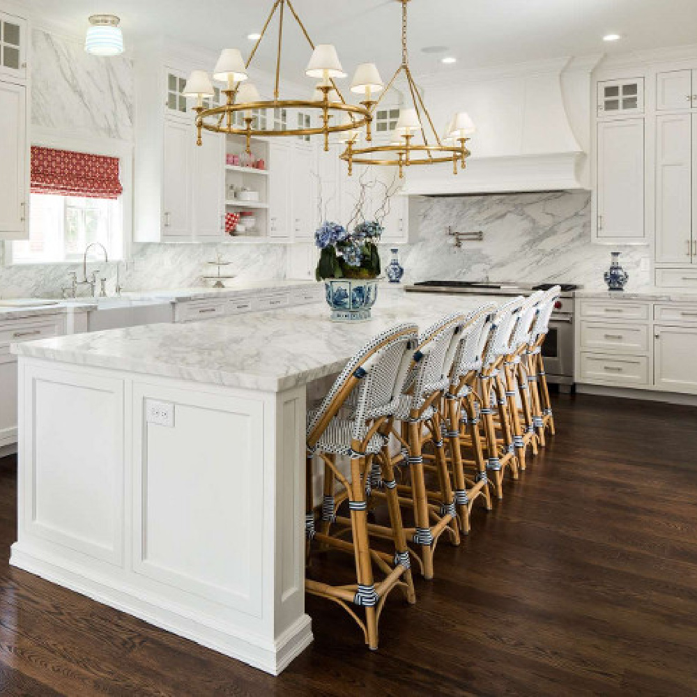 Luxurious kitchen by The Fox Group with Parisian bar stools, ring style chandeliers over island, and white cabinetry. #thefoxgroup #kitchendesign #timelessdesign