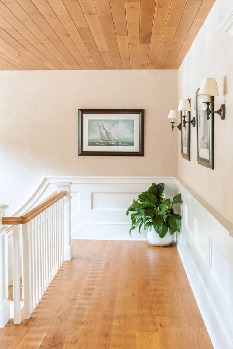 Beautiful wide plank flooring (white oak) on a staircase landing with paneled wainscot and pale peachy walls. #whiteoak #flooring #hardwoodfloor #carlisle #woodplankfloors #interiordesign #carlisle #staircase