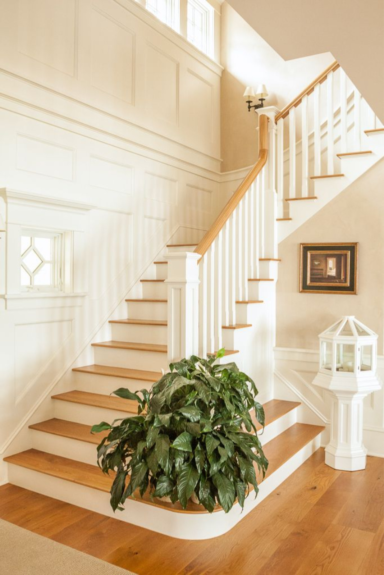 Stunning white oak wide plank flooring on a staircase in a grand coastal style home with white trim. #flooring #interiordesign #whiteoak #staircase #wideplankfloors #hardwoodfloor #carlisle #coastalstyle