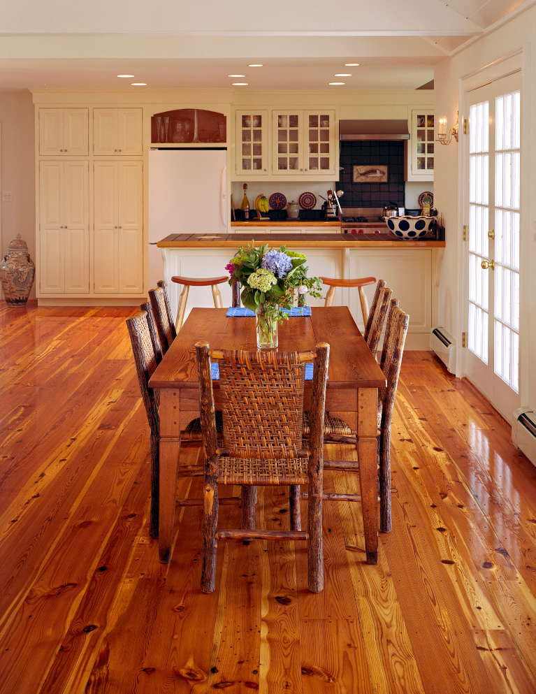 Reclaimed Heart Pine flooring (wide plank by Carlisle) plays a starring role in this casual country breakfast area. adjacent to a white kitchen. #hardwoodflooring #reclaimed #wideplank #flooring #carlisle #heartpine #interiordesign #rusticfloor