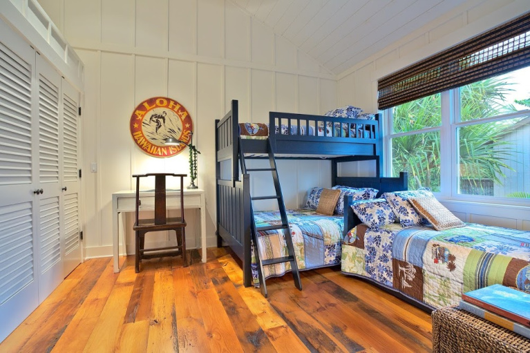 Reclaimed barnwood flooring adds rusticity in a cheerful bunk room with navy beds and a Hawaiian theme. #wideplankflooring #carlisle #hardwoodfloor #interiordesign #reclaimed #barnwood #bunkroom
