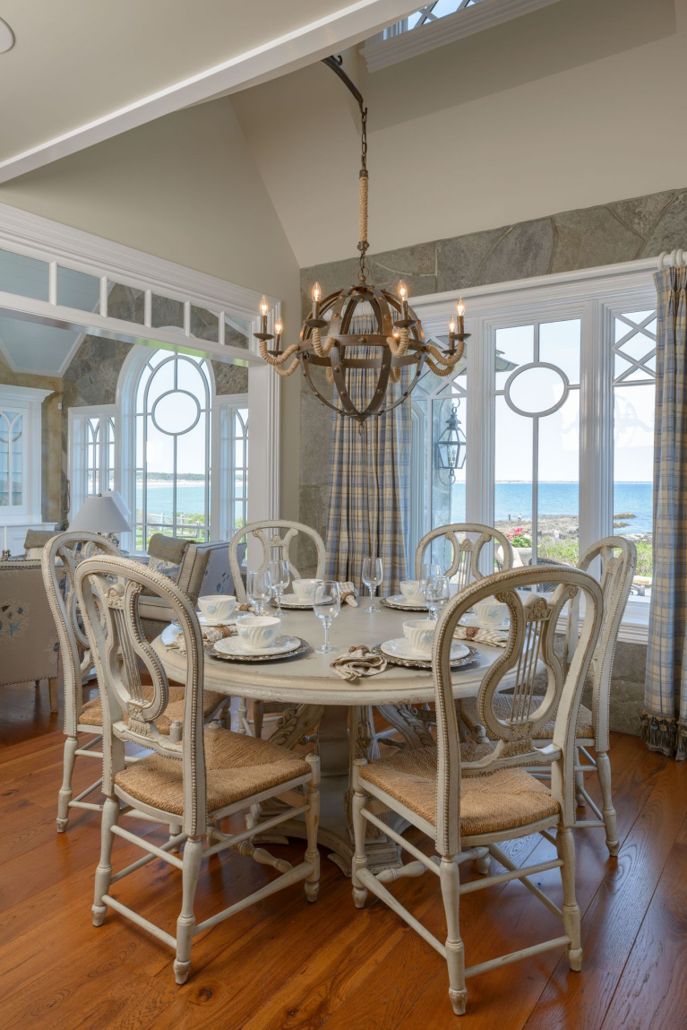 Hickory wide plank flooring in a coastal style dining room with French country decor, spectacular windows, and a majestic view. #flooring #wideplankflooring #hickory #hardwoodfloor #diningroom #coastalstyle #carlisle #interiordesign