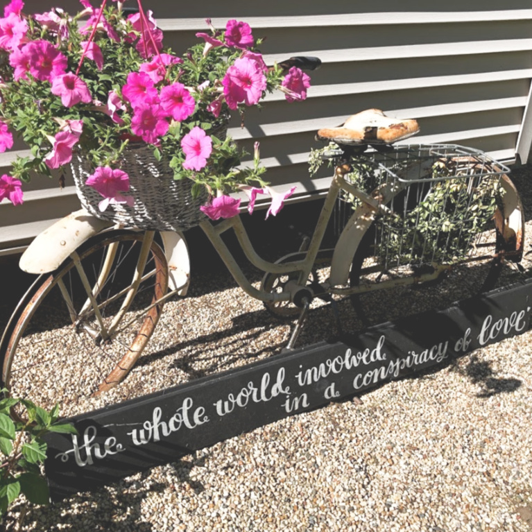 Vintage bicycle with basket full of pink petunias and hand lettered sign: The Whole World Involved in a Conspiracy of Love. #hellolovelystudio #courtyard #summergarden #gardendecor