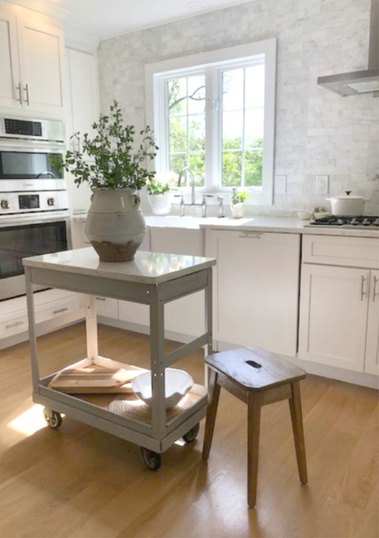 Hello Lovely Studio's serene white kitchen with vintage steel cart repurposed as a work table. #hellolovelystudio #whitekitchens #modernfarmhouse #coastal #shakerkitchen #vintagecart #worktable