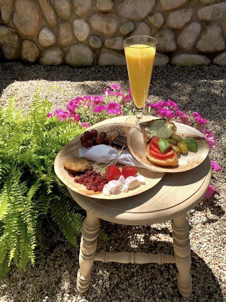Sweet and savory nibbles and mimosa served on a rustic stool doubling as a cocktail table in the garden - Hello Lovely Studio. #hellolovelystudio #outdoorentertaining #summerentertaining #appetizers #rusticstool #gardenparty