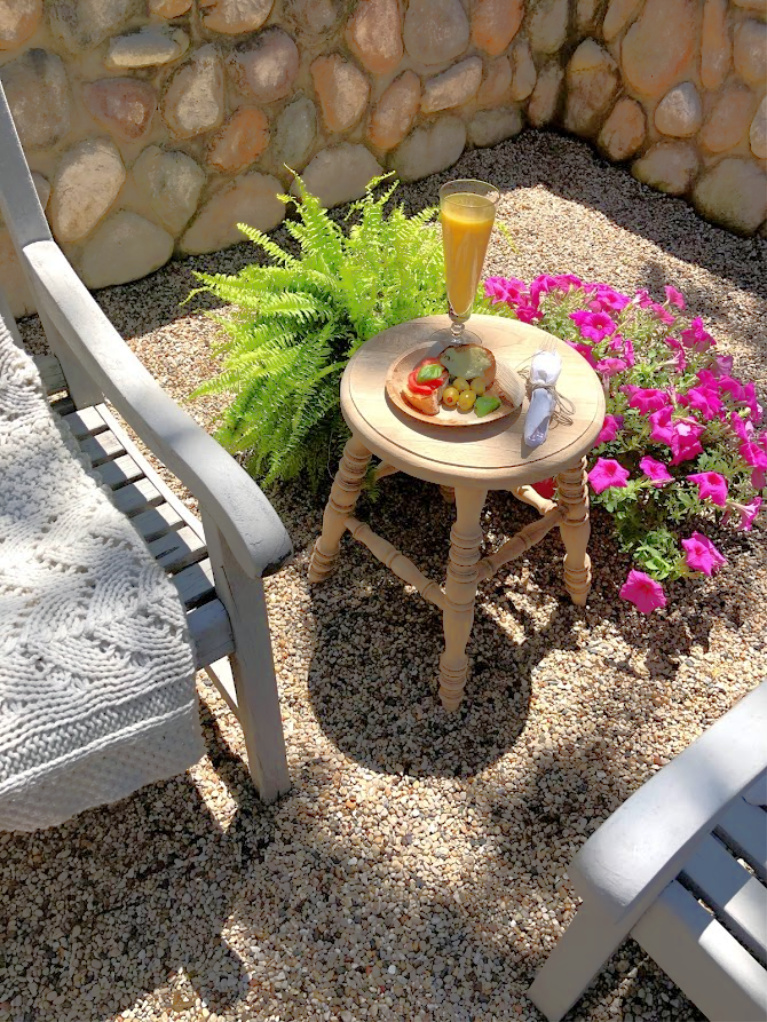 Savory snacks on a disposable plate made from palm leaves upon a rustic wood stool used as side table in our French inspired courtyard - Hello Lovely Studio. #hellolovelystudio #frenchcountry #courtyard #summergarden #rusticstool
