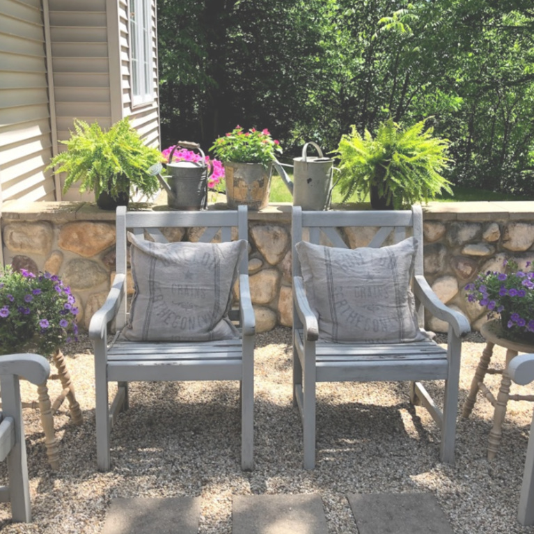 Our French country courtyard in summer with painted wood furniture, grainsack pillows, and pea gravel. #hellolovelystudio #frenchcountry #courtyard #garden #outdoorliving #summer