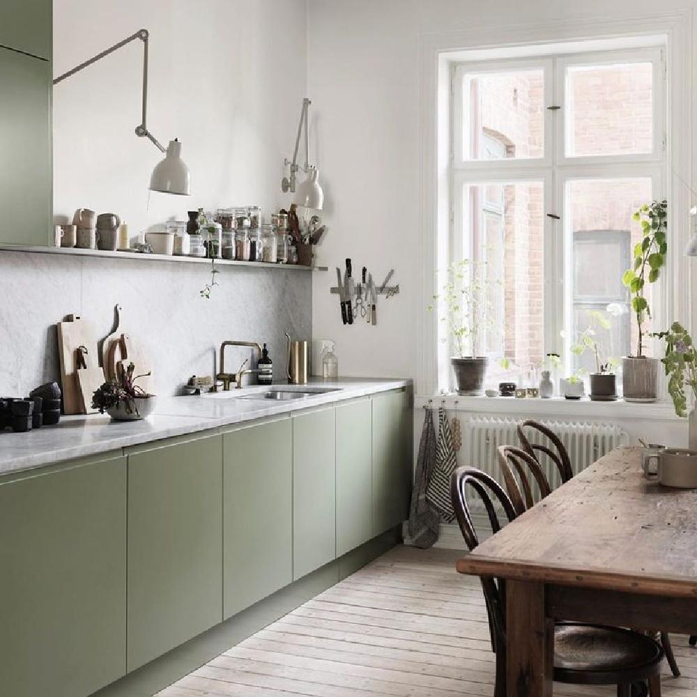 Serene sage green Scandinavian kitchen with mossy green cabinets and modern adjustable arm sconces - Petra Bindel. #swedishkitchen #scandinaviandesign #nordicstyle #europeancountry #kitchendesign