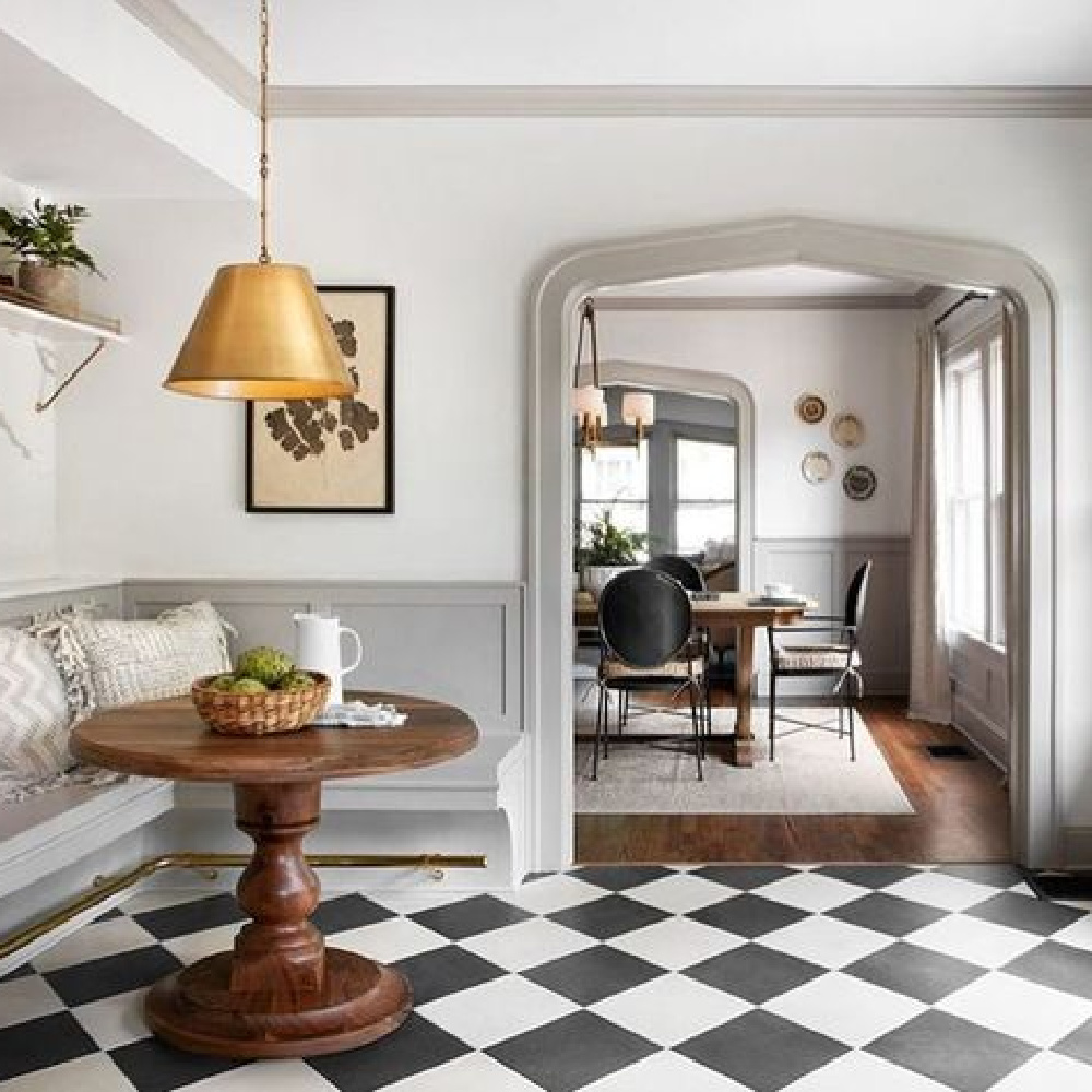 Scrivano fixer upper cottage breakfast nook with European inspired design, black and white check floors, light grey trim, white walls, modern lighting, and romantic timeless style. #homedecor #vintagestyle #fixerupper #kitchendesign #vintagekitchen #europeancountry