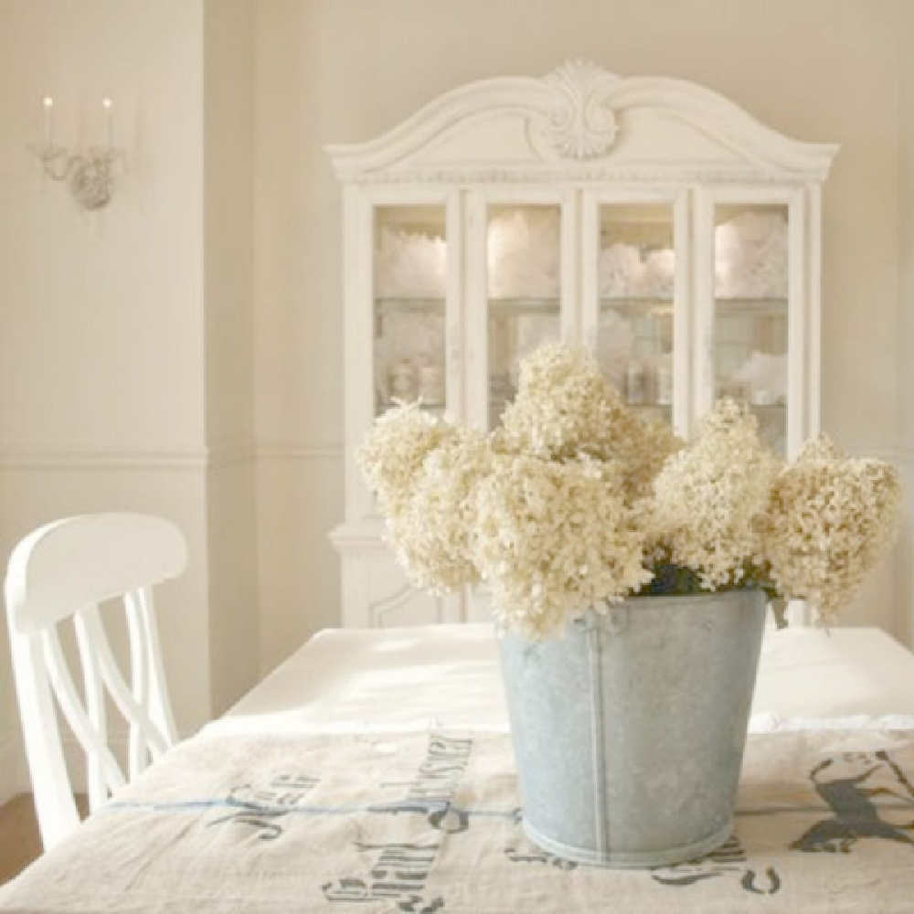 Benjamin Moore White Sand paint color on walls of my French country dining room with dried hydrangea in vintage bucket on table with grainsack runner - Hello Lovely Studio. #frenchcountry #diningroom #paintcolors #benjaminmoorewhitesand #whitesand #interiordesign