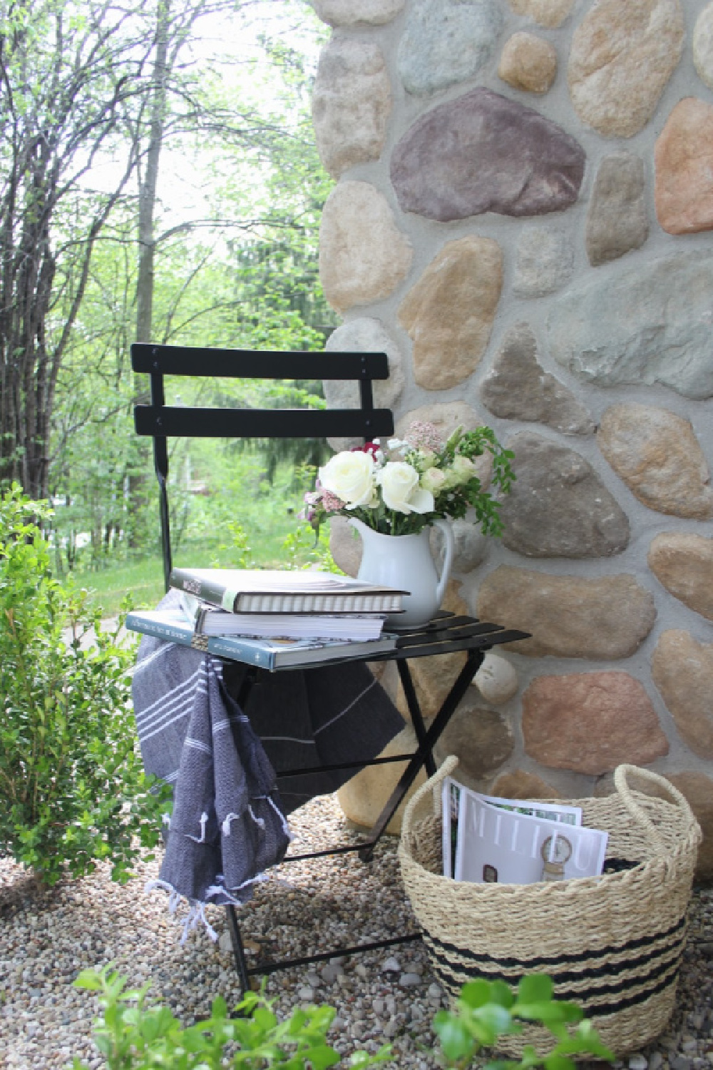 French bistro chair and stripe Turkish throw tucked in a corner of my garden to invite relaxation and reading (cookbooks are my idea of relaxation!). #hellolovelystudio #frenchcountry #bistrochair #turkishthrow #seagrassbasket #turkishtowel #outdooroasis #romanticgarden #outdoordecor #bistrochairs