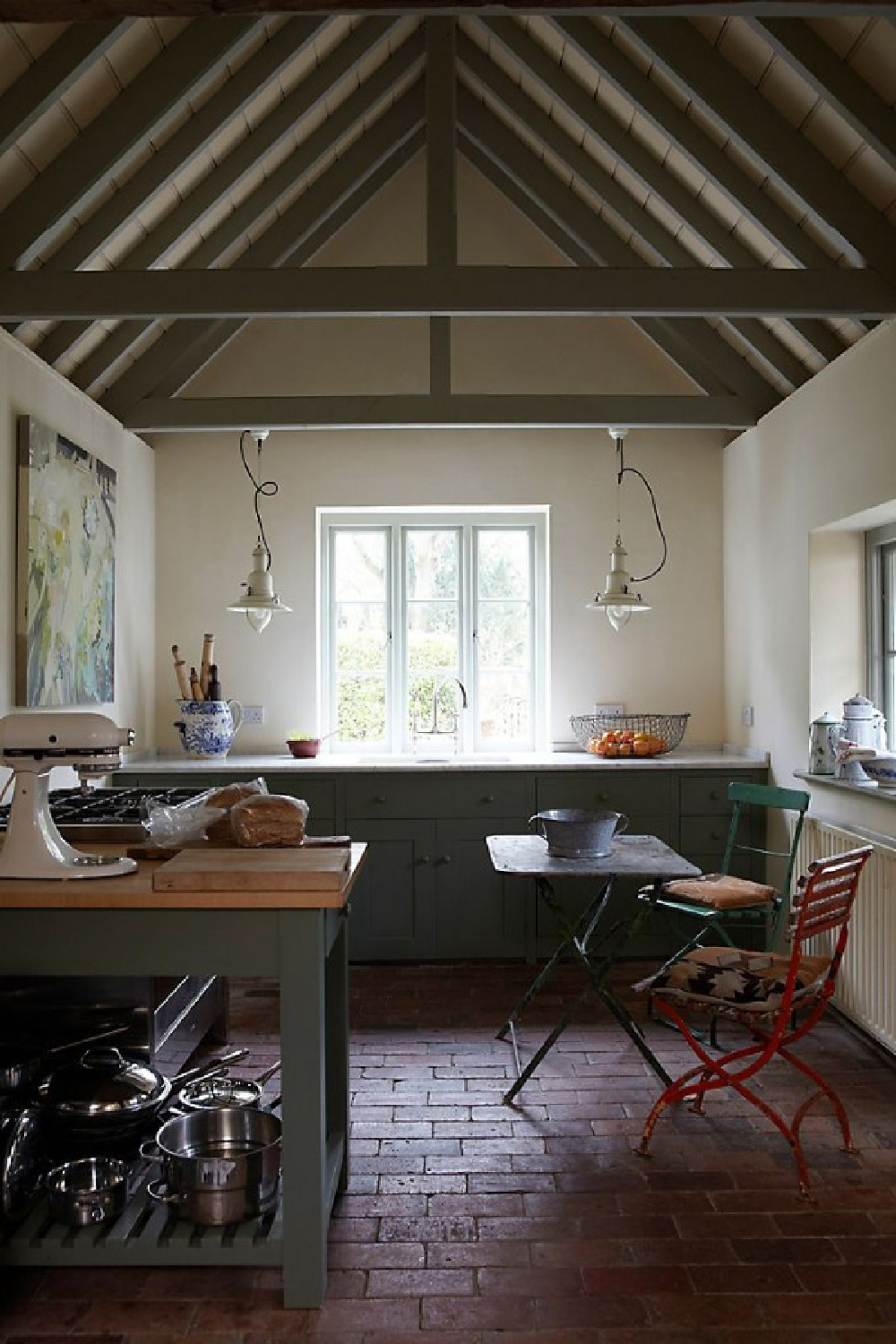 Pointing by Farrow & Ball is a paint color used on the walls of this English country kitchen with rustic ceiling trusses and farmhouse pendants. #pointing #farrowandball #paintcolors #calmpaintcolors #interiordesign