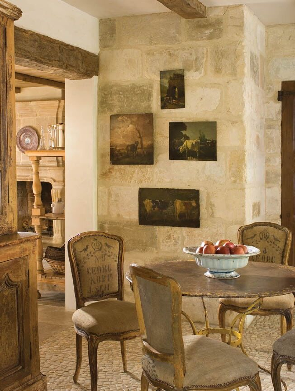 Pale tone on tone palette with reclaimed limestone walls and floors in a modern French breakfast dining room (Chateau Domingue). #oldworldstyle #europeancountry #modernfrench #frenchfarmhouse