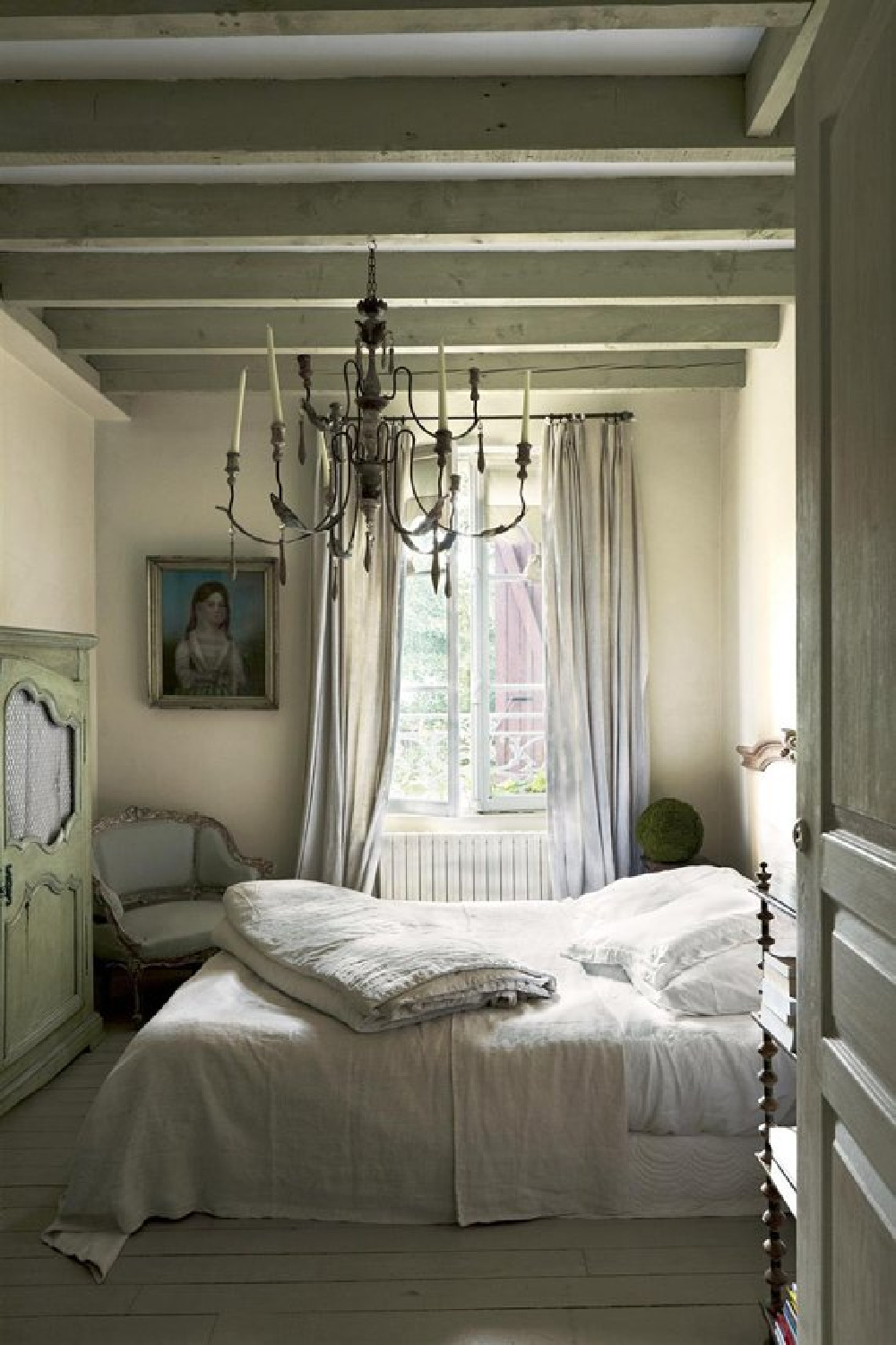 Ball Green by Farrow & Ball paint on the ceiling of a beautiful French country bedroom with chandelier and beams. #frenchcountry #frenchfarmhouse #interiordesign #farrowandball #ballgreen #paintcolors