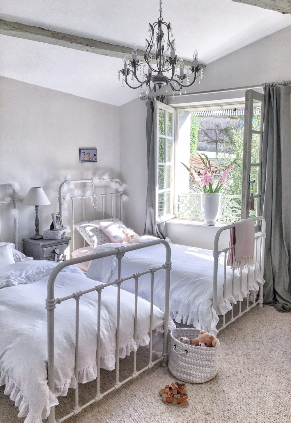 Charming French farmhouse girl's bedroom with iron panel beds and windows open to countryside - Vivi et Margot. #frenchfarmhouse #bedrooms #girlsbedroom