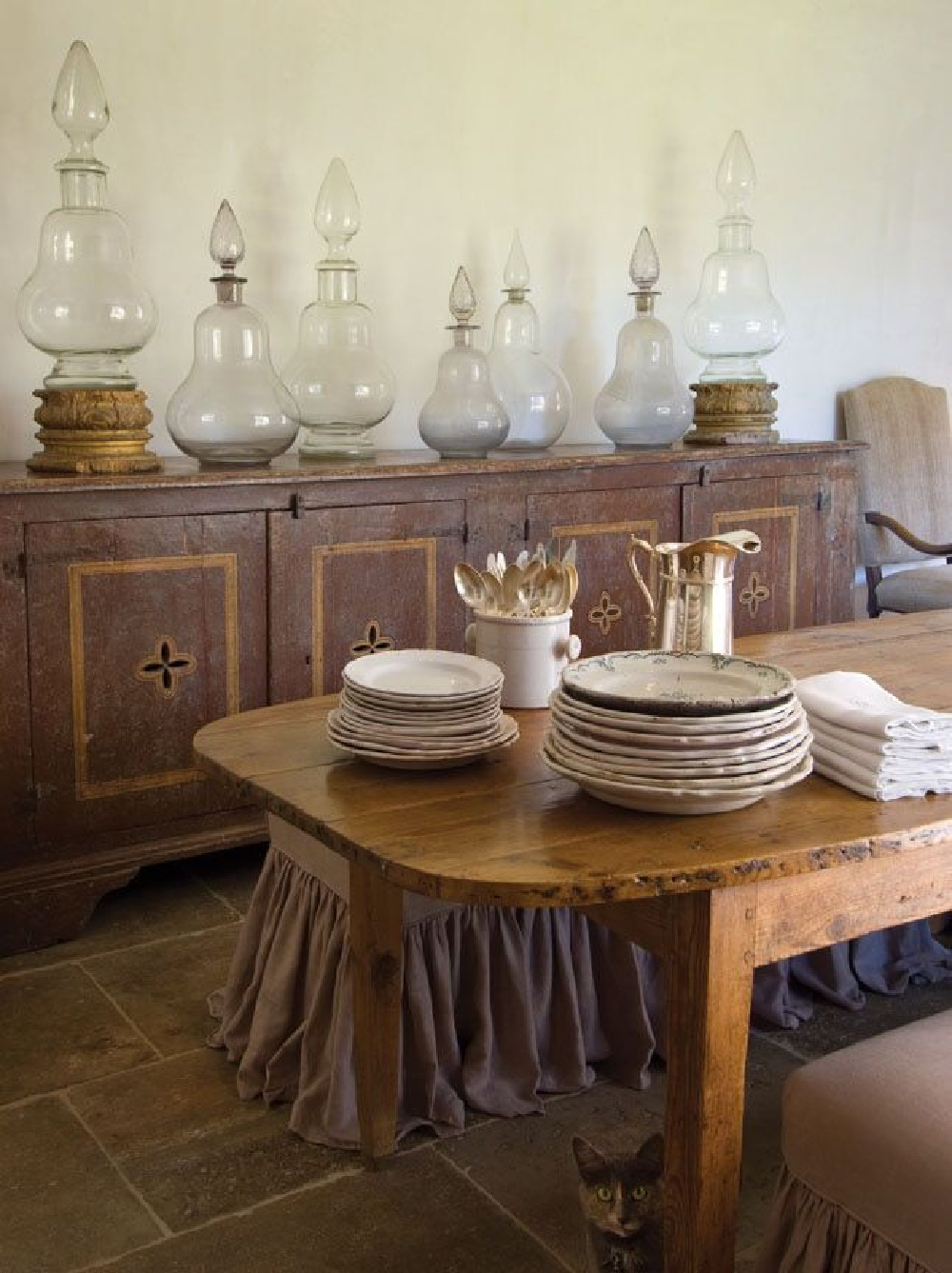 Old apothecary jars, rustic antiques from Europe, and a concerned kitty too in a dining room by Chateau Domingue. #diningrooms #interiordesign #countryfrench