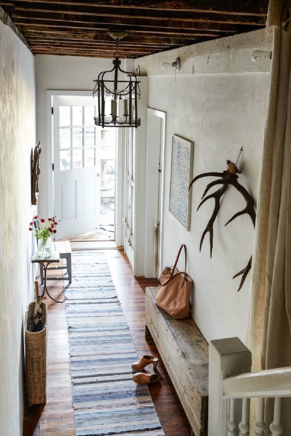 Gorgeous European farmhouse style in a New York apartment entry with rustic finishes and antiques by Jocelyn Sinnauer.