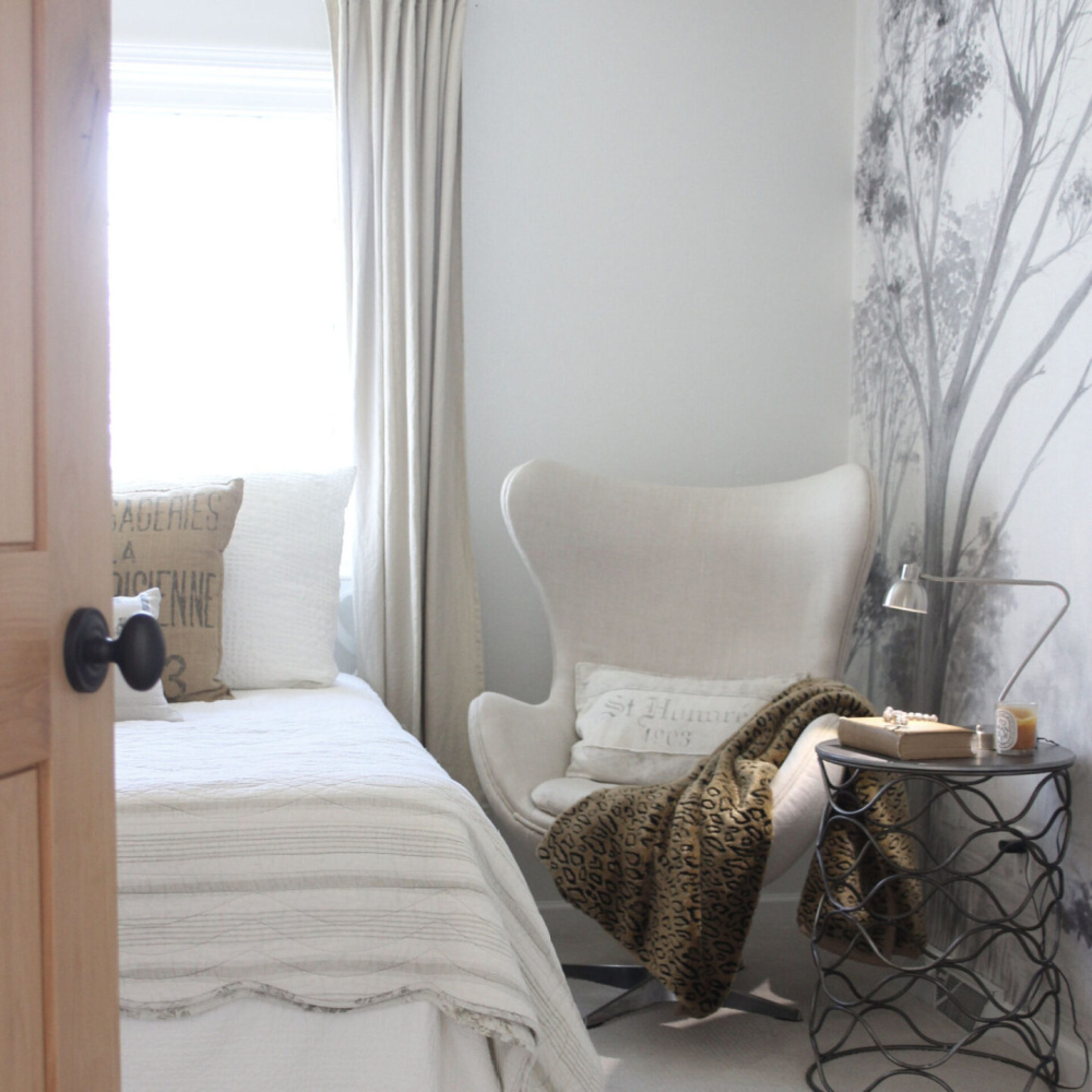 Alder door opens into a neutral bedroom with linen upholstered egg chair and grisaille mural on wall - Hello Lovely Studio.