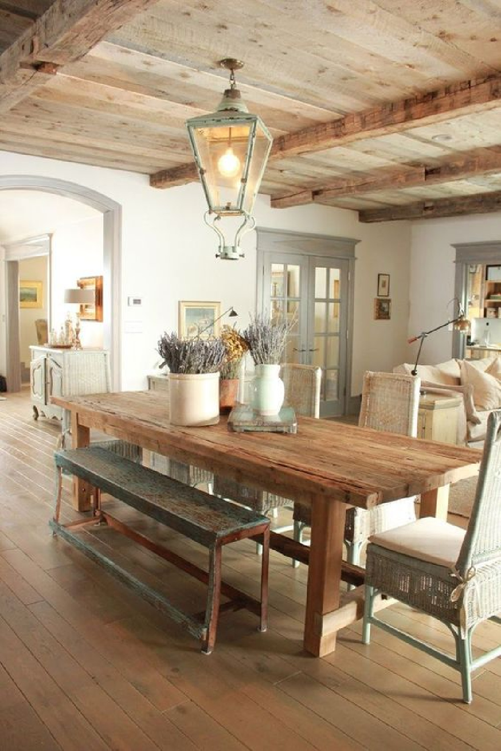 Rustic elegance and uncluttered country decor sing in a French Nordic Farmhouse dining room with knotty wood ceiling and antique lantern. See more European inspired country decor in the story. #FrenchCountry #FrenchNordic #countrydecor