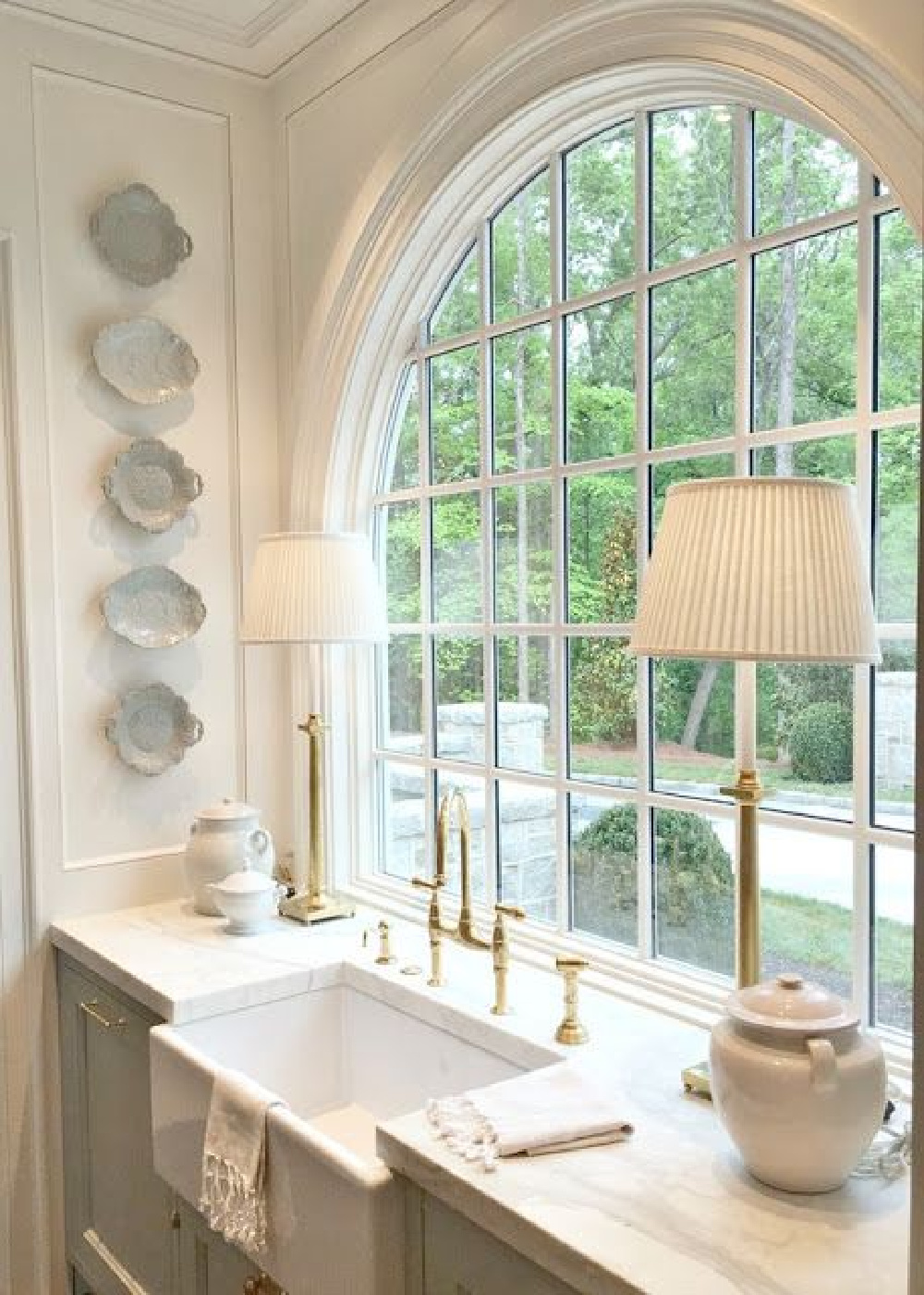 Elegant, refined, and masterfully designed, this kitchen with farm sink and arched window is but one moment in our tour of unforgettable interiors with European inspired charm. #farmsink #FrenchCountry #lightblue
