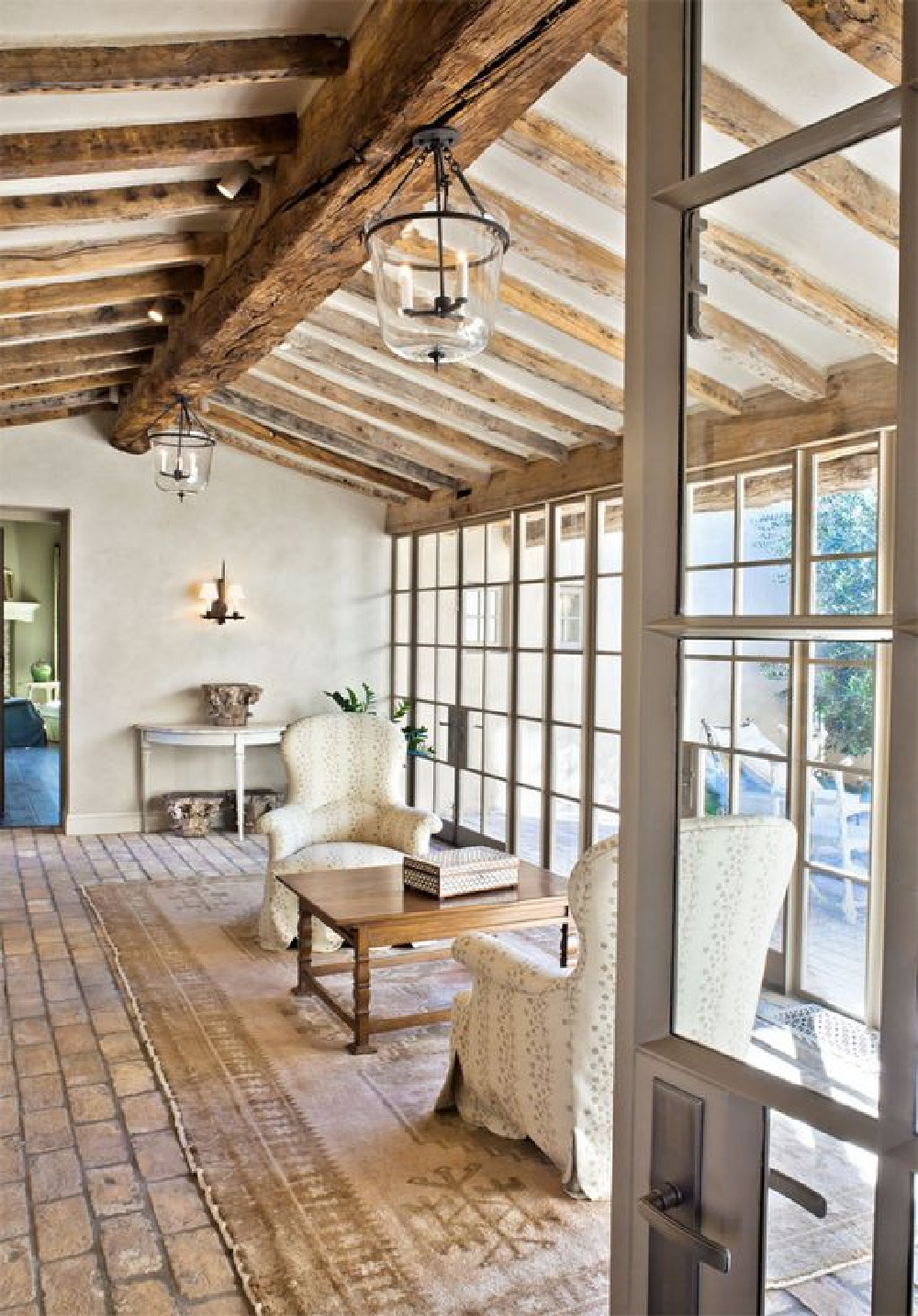 Rustic aged wood ceiling beams, brick flooring and walls of glass in a masterfully designed European country home - Oz Architects.
