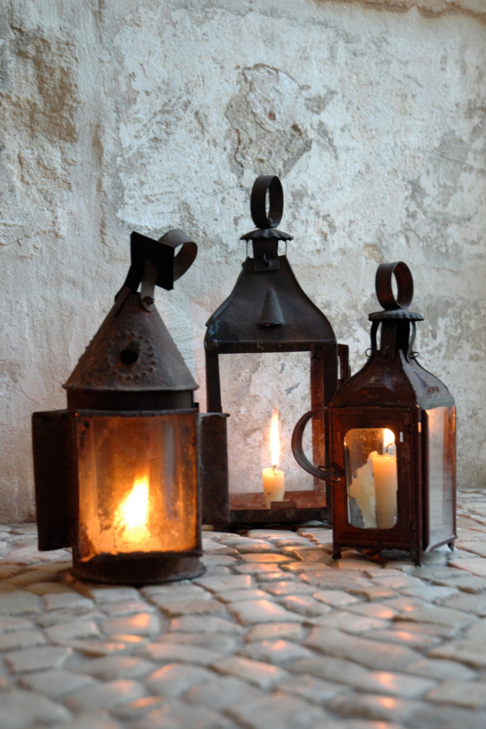Charming antique French lanterns with candles glowing inside - Chateau Domingue. #countryfrench #antiquelanterns #bronzelantern