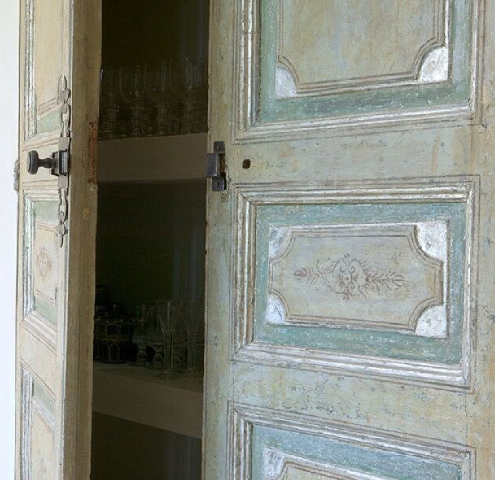 Beautiful painted antique French wood doors in the home of Ruth Gay - Chateau Domingue. #oldworldstyle #antiquedoors #frenchdoors