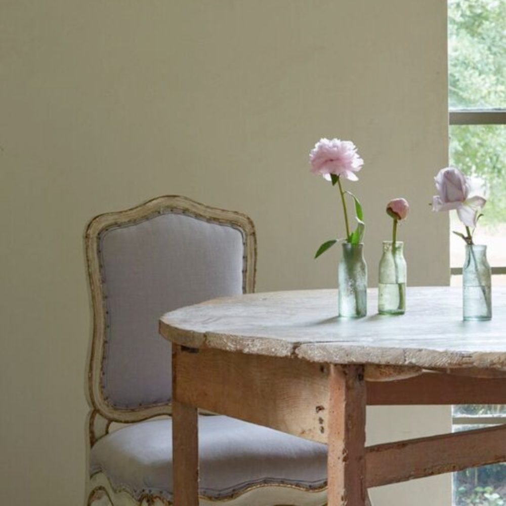 Rustic round antique farm table accented with lovely and simple bottle vases - Chateau Domingue. #frenchcountry #romanticinteriors