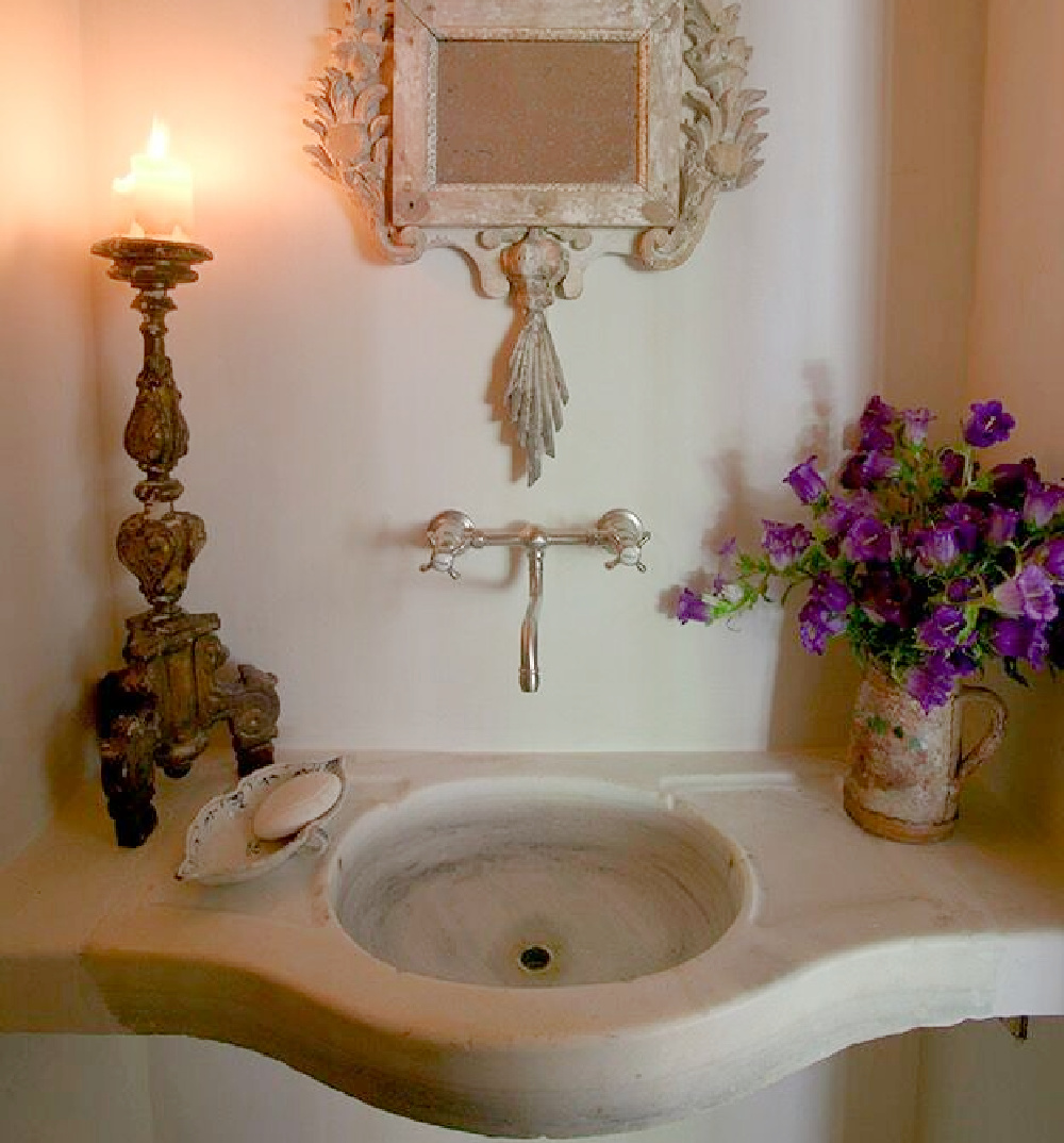 Antique stone sink, ancient candlestick and ornate mirror in a country French bath - Chateau Domingue.